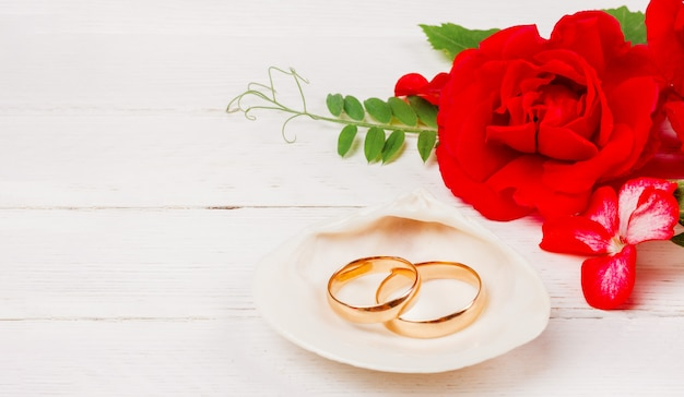 Gold wedding rings in a white seashell and red rose flowers on a white wooden background with copy space Premium Photo