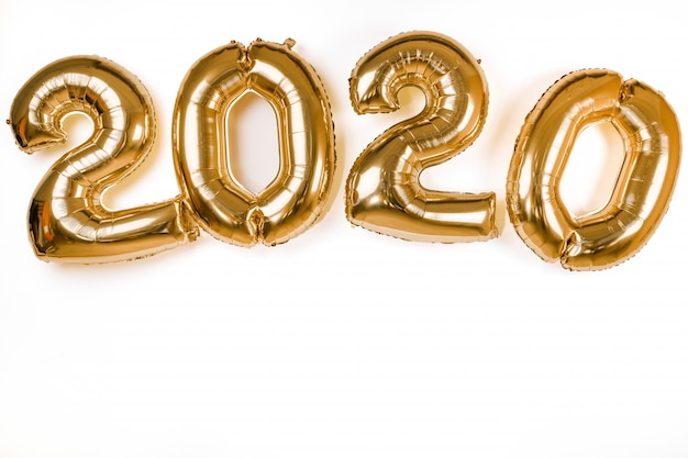 Golden 2020 new year balloons isolated over white wall Premium Photo