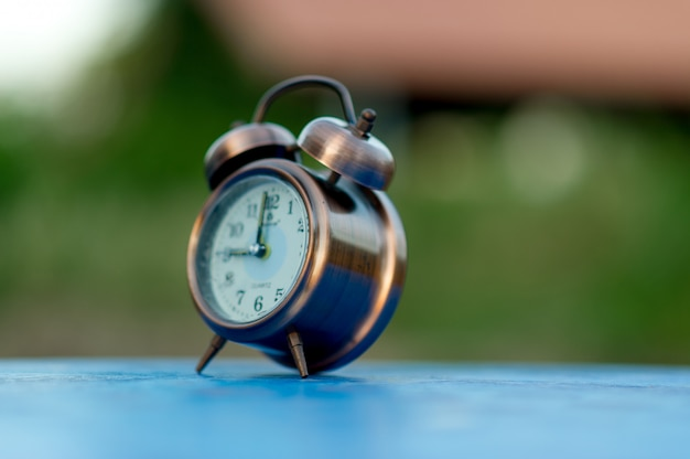 Golden alarm clock picture placed on a blue table, green background Premium Photo