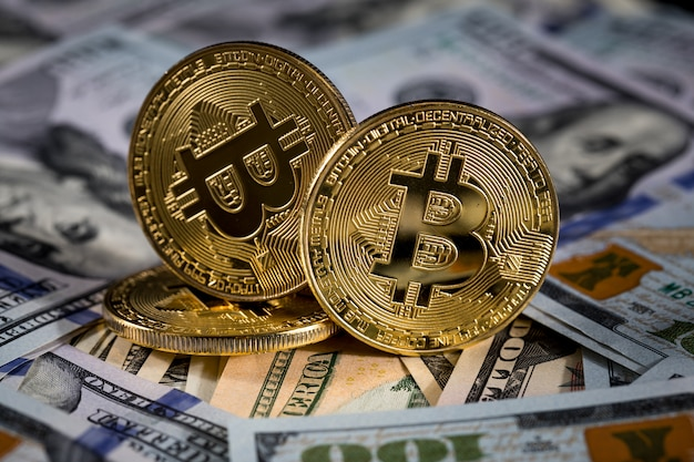 Golden bitcoin coin on us dollars close up. electronic crypto currency Premium Photo
