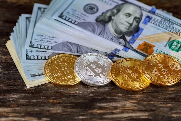 Золотые монеты биткойн на бумажных долларах деньги виртуальная валюта. Premium Фотографии