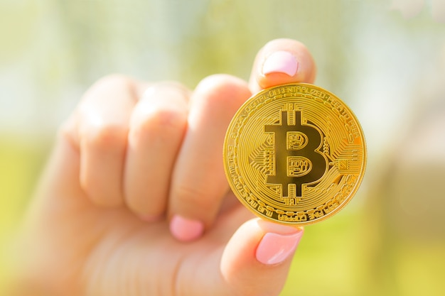 Golden bitcoin in girls hand with pink nails outside Premium Photo