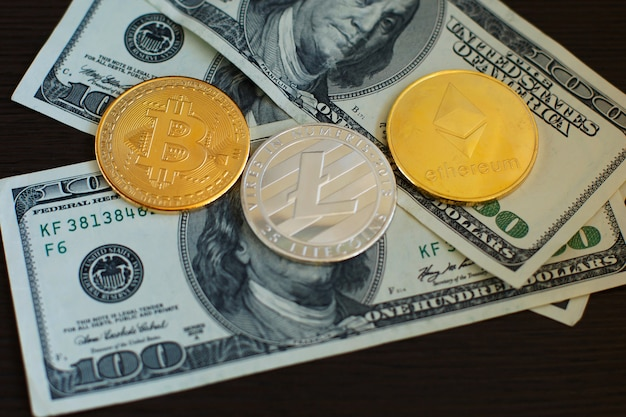 Golden bitcoin, silver litecoins and ethereum on us dollars close up. Premium Photo