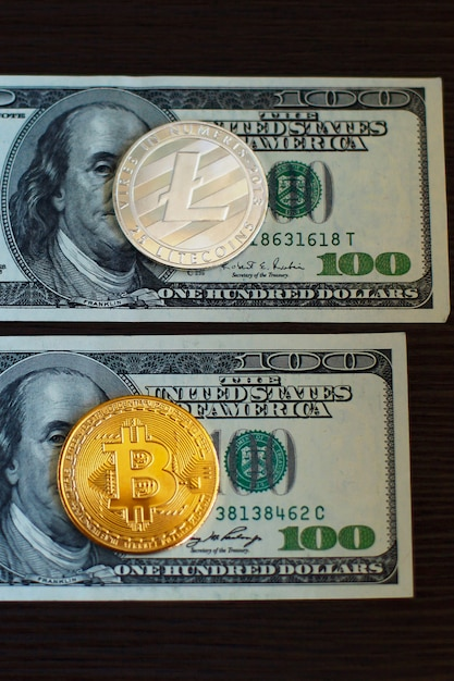 Golden bitcoin and silver litecoins on us dollars close up. Premium Photo