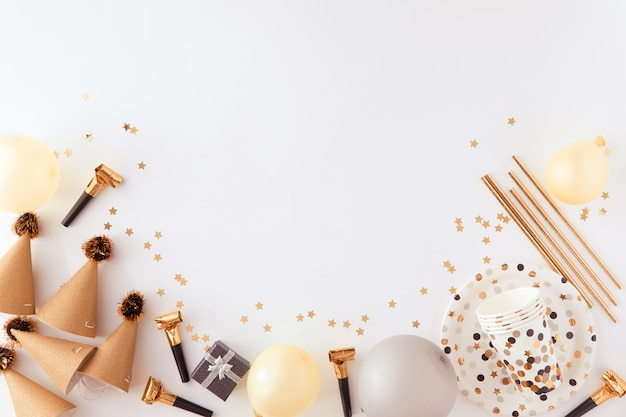 Golden and black decorations for the party on white backgroud. Premium Photo