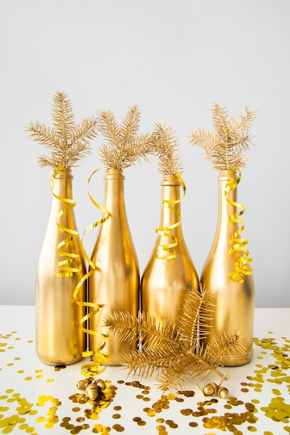 Golden bottles with ribbons and pine leaves Free Photo