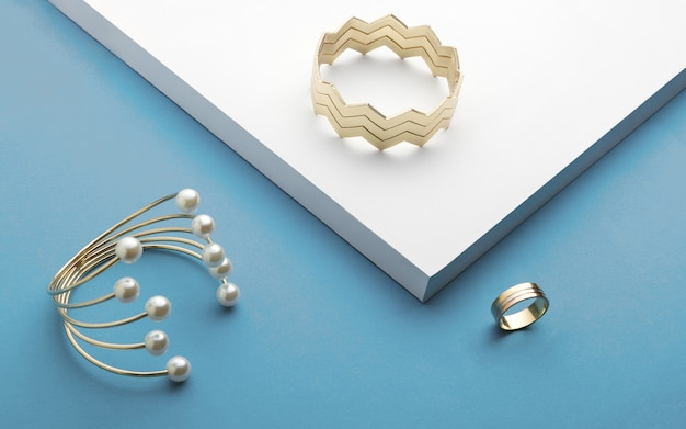 Golden bracelets and golden ring on white and blue background - zigzag bracelet and pearl golden bracelet Premium Photo