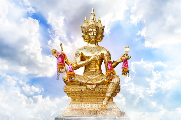 Golden of brahma statue religious with blue sky with white spindrift very clouds background of thailand. Premium Photo