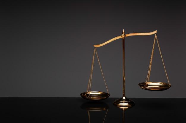 Golden brass balance scale on black background Premium Photo