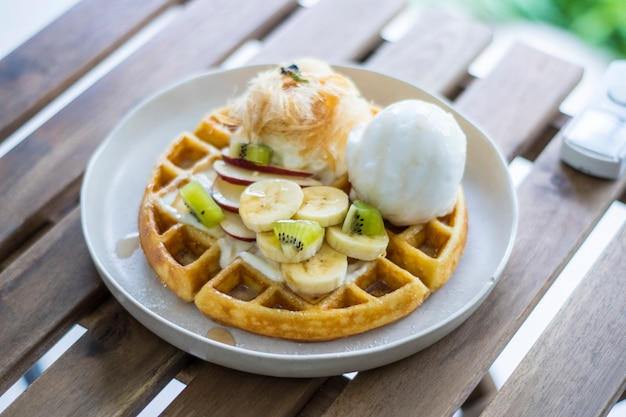 Golden brown waffle topped with ice cream fruit sliced and whipped cream and cotton candy Premium Photo