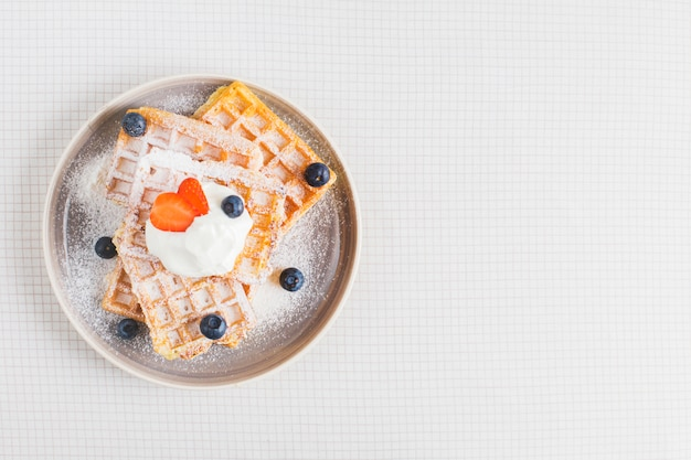 Golden brown waffle topped with sliced strawberries; blueberries and whipped cream on plate Free Photo