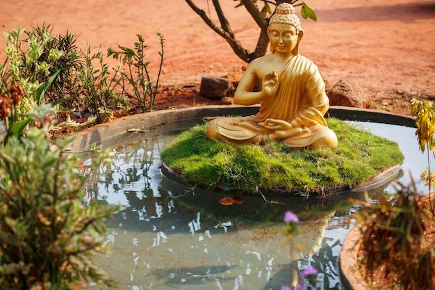 Golden buddha statue by the pond in goa Premium Photo