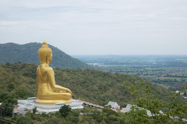 Golden buddha statue on mountain with sky Premium Photo