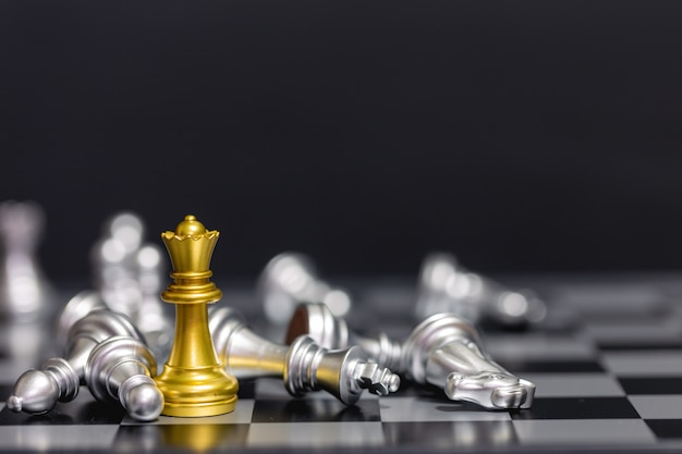 Golden chess pieces beat the silver chess team on a black background Premium Photo