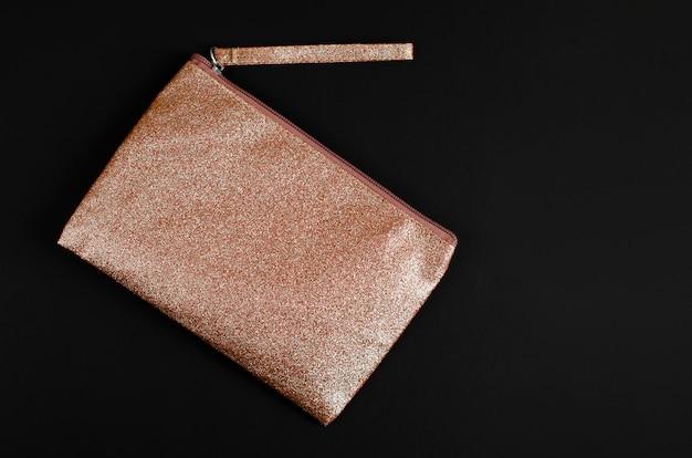Golden cosmetic bag on black . Premium Photo