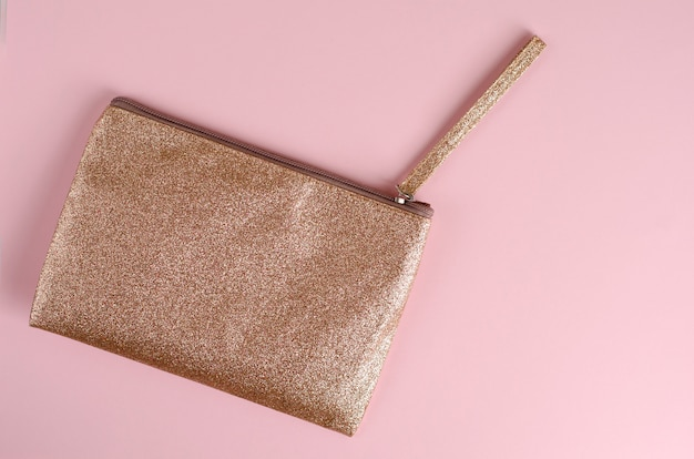 Golden cosmetic bag on pastel pink Premium Photo