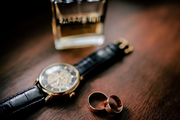 Golden cufflings, wedding rings and watch lie on wooden table Free Photo