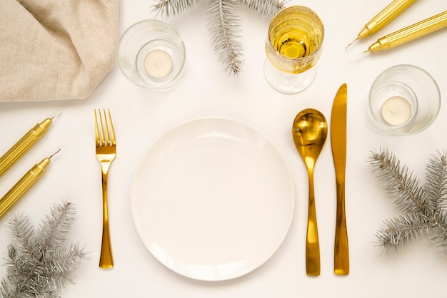 Golden cutlery and copy space plate Free Photo