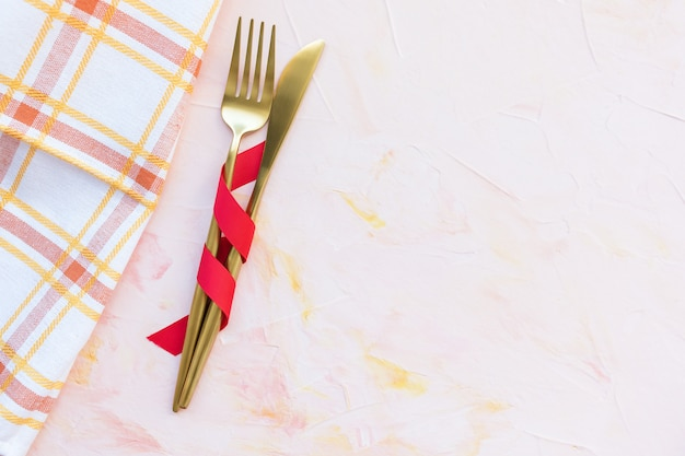 Golden cutlery in red ribbon and kitchen towel on a pink Premium Photo