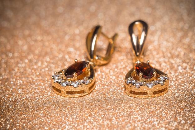 Golden earrings with garnet Premium Photo