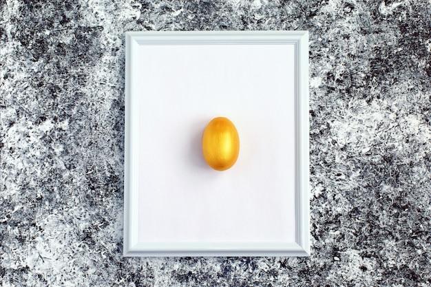 Golden egg on white frame Premium Photo