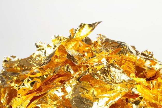 黄金箔の部分、白で隔離される光沢のある包装紙の装飾要素の束 無料写真