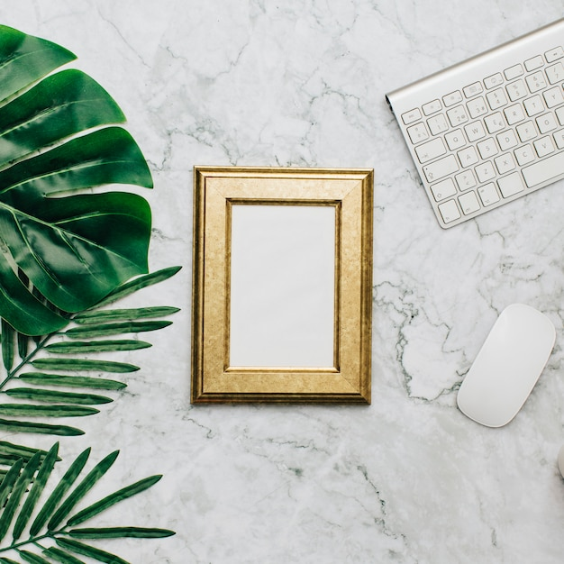 Golden frame on marble desktop and tropical leaves Free Photo