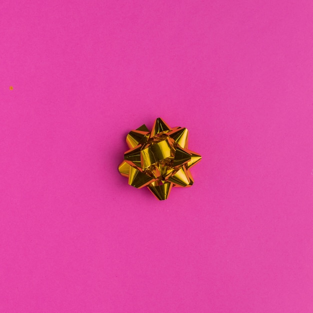 Golden gift bow on bright pink background Free Photo