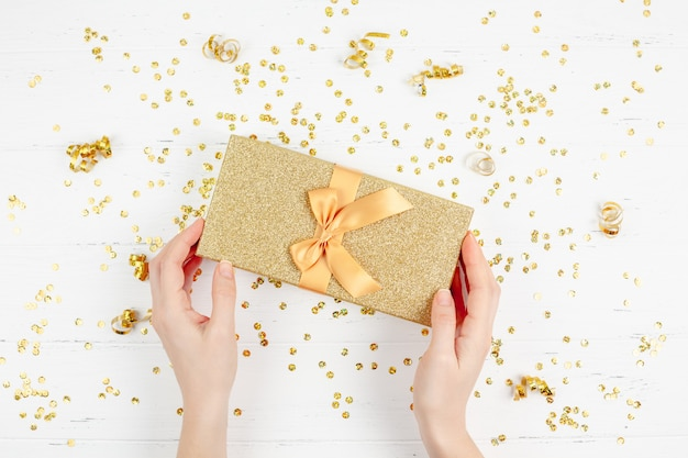 Golden gift box with confetti Premium Photo