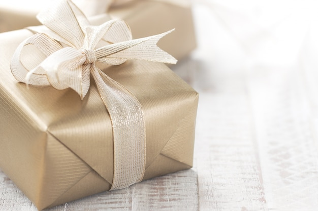 Golden gift with a white bow Free Photo