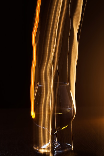Golden glass of whiskey and yellow lines Free Photo