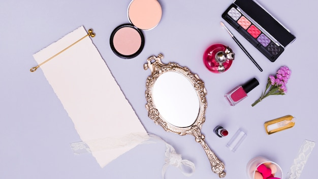 Golden hair stick on blank white torn paper with cosmetic products and hand mirror on purple background Free Photo