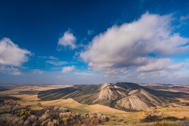 Золотые холмы, маленькие горы на фоне голубого неба с облаками Premium Фотографии