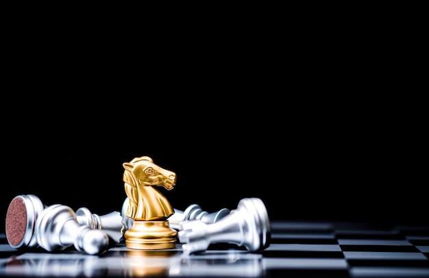 Golden horse chess stand alone with fallen silver chess pieces. winner of business competition and marketing strategy planing concept. Premium Photo