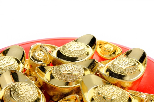 Golden ingots on red tray isolate at white.chinese language on ingot mean Premium Photo