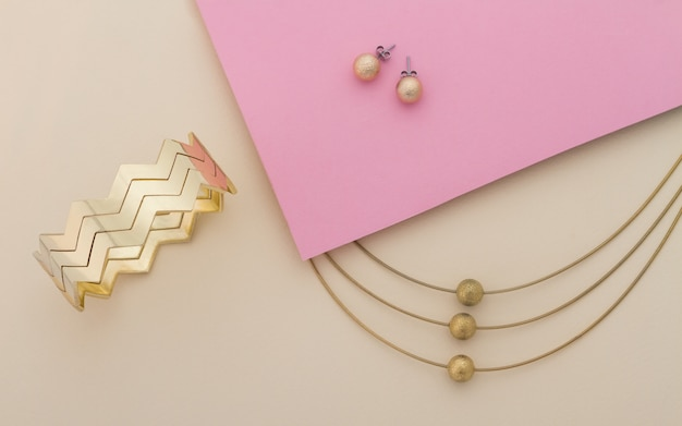 Golden jewelry set on pink and beige background Premium Photo