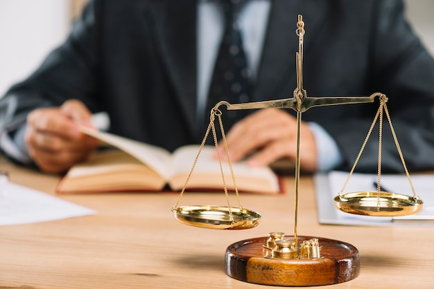 Golden justice scale in front of lawyer reading book on table Free Photo
