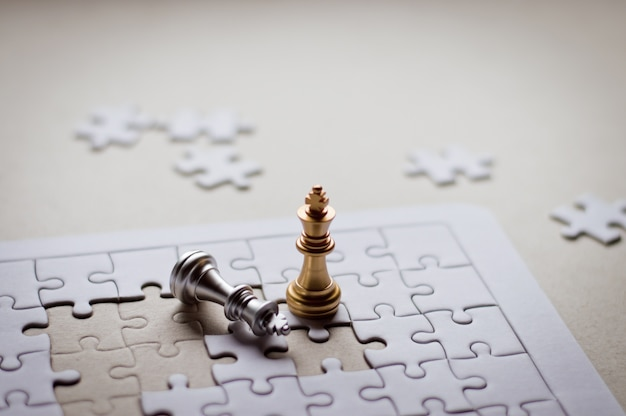 Golden king chess piece win the silver king chess on jigsaw for business and finance. Premium Photo