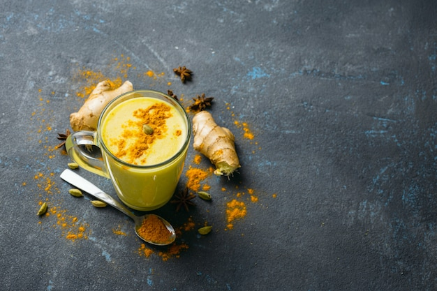 Golden latte on black table  top view. ingredients for cooking yellow latte Premium Photo