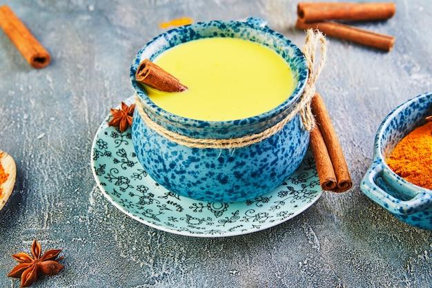Золотой латте турмерин здоровый напиток в синей чашке. Premium Фотографии