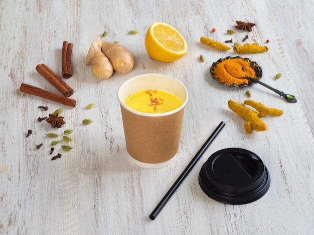 ウコン、シナモン、生姜、レモン、コショウで紙コップに黄金のミルク。抗ウイルス感染の予防 Premium写真