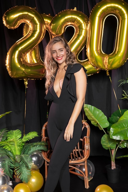 Golden new year 2020 balloons and beautiful girl Free Photo