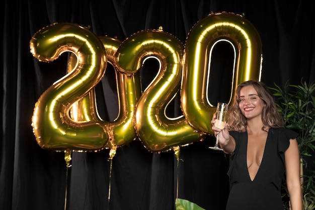Golden new year 2020 balloons and cute girl holding a glass of champagne Free Photo
