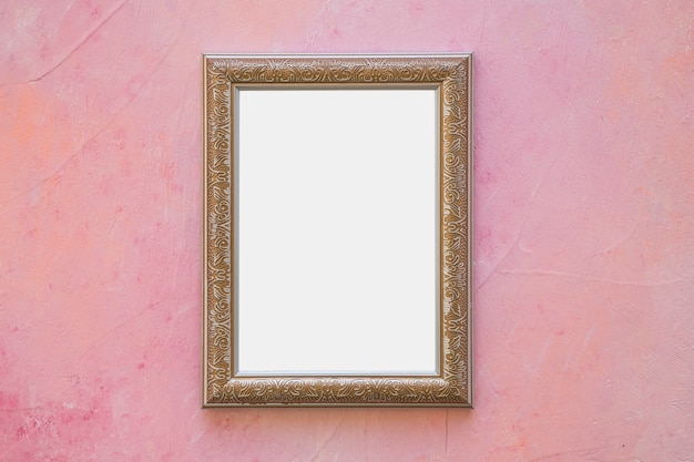 Golden ornate white frame on pink wall