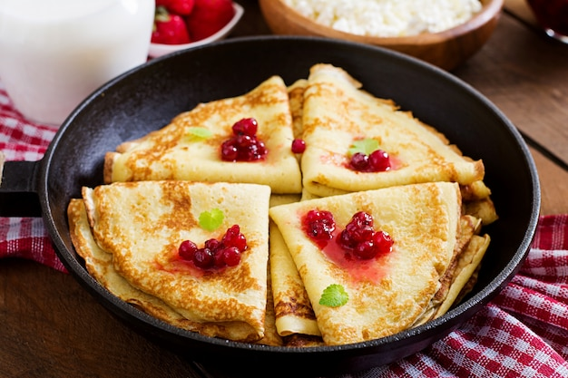Golden pancakes with cranberry jam and honey in a rustic style. top view Free Photo
