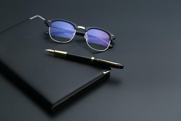 Golden pen,notebook,calculator and glasses on black desk Photo
