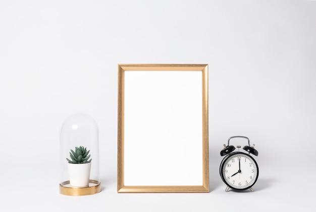 Golden photo frame mock up and clock interior decor home elements. Premium Photo