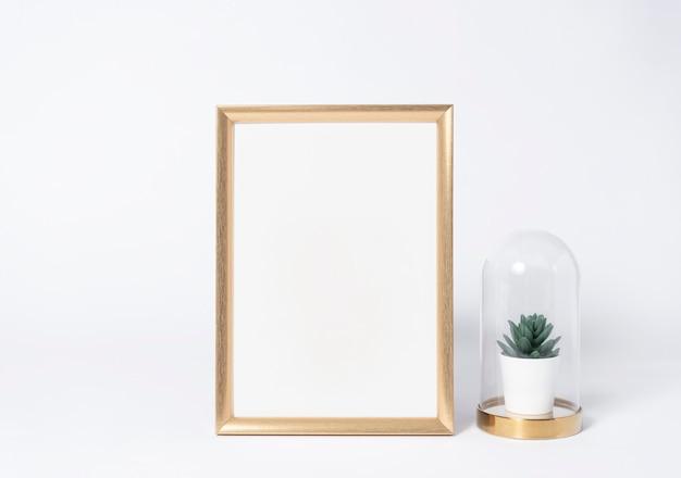 Golden photo frame mock up and plants in vase interior decor home elements. Premium Photo