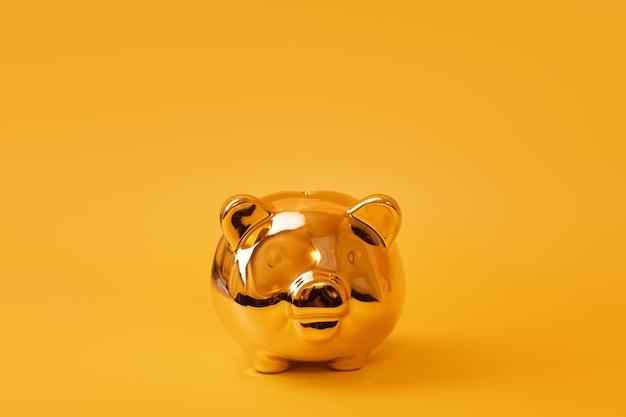 Золотая копилка на желтом фоне. золотая копилка. денежная свинья, экономия денег, копилка, концепция финансов и инвестиций. свободное место для текста. Premium Фотографии