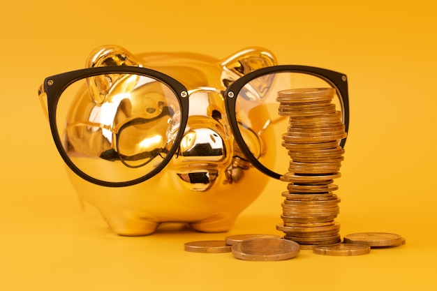 Golden piggy bank wearing glasses with money tower Premium Photo
